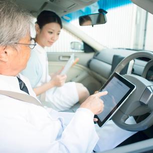 車の中でタブレットPCを見る医者と看護師(訪問医療)の写真素材 [FYI02847266]