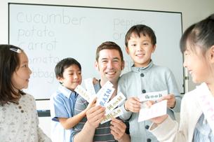 英語の勉強をする小学生と外国人教師の写真素材 [FYI02847364]
