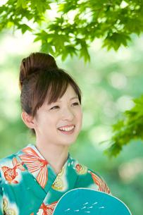 うちわを持ち微笑む女性の写真素材 [FYI02847384]