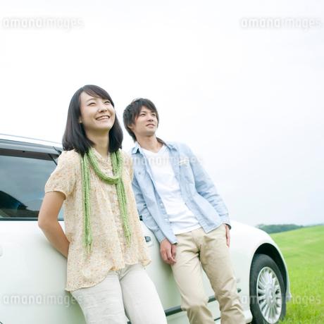車の側で微笑むカップルの写真素材 [FYI02847416]