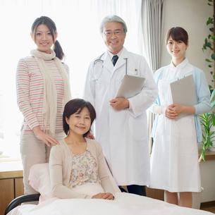 ベッドで微笑む患者と医者と看護師(訪問医療)の写真素材 [FYI02847453]
