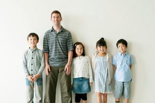 壁際に並ぶ小学生と外国人教師の写真素材 [FYI02847454]