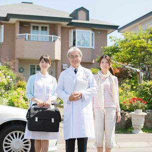 家の前に並ぶ医者と看護師と患者の家族(訪問医療)の写真素材 [FYI02847484]
