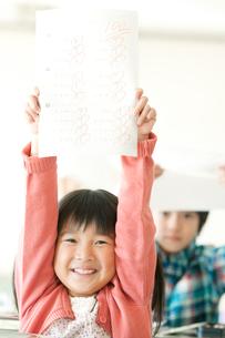 テストを持ち微笑む小学生の写真素材 [FYI02847523]