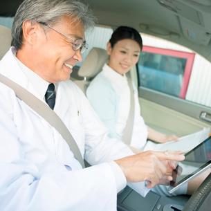 車の中でタブレットPCを見る医者と看護師(訪問医療)の写真素材 [FYI02847657]