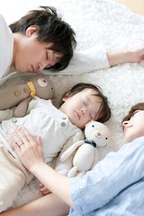 赤ちゃんと共に眠る夫婦の写真素材 [FYI02847711]