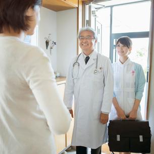 玄関で医者と看護師を出迎える患者(訪問医療)の写真素材 [FYI02847743]