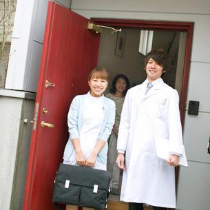 玄関前で微笑む医者と看護師と患者(訪問医療)の写真素材 [FYI02848052]