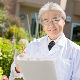 家の前でカルテを持ち微笑む医者(訪問医療)の写真素材 [FYI02848063]