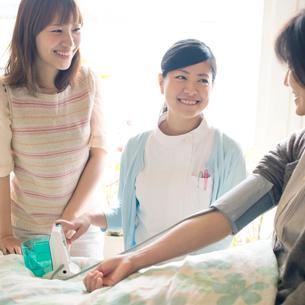 患者の血圧を測る看護師(訪問医療)の写真素材 [FYI02848132]