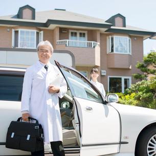 タブレットPCを持ち車の前に立つ医者(訪問医療)の写真素材 [FYI02848139]