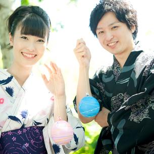 ヨーヨーを持ち微笑むカップルの写真素材 [FYI02848158]