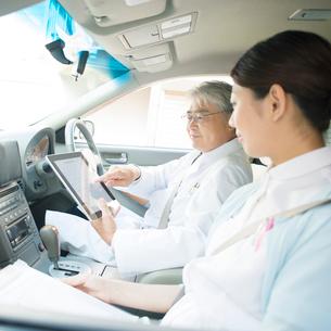 車の中でタブレットPCを見る医者と看護師(訪問医療)の写真素材 [FYI02848247]