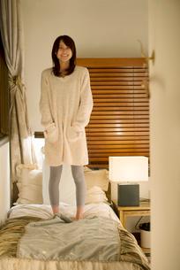 ベッドの上に立ち微笑む女性の写真素材 [FYI02848305]