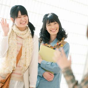 手を振り微笑む大学生の写真素材 [FYI02848319]