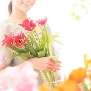 花瓶に入った花を持ち微笑む花屋の店員の写真素材 [FYI02848387]