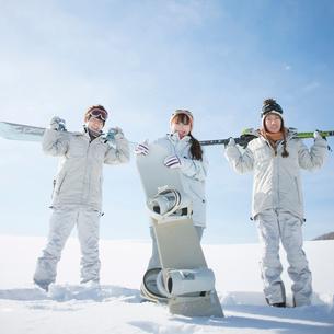 スノーボードとスキーを持ち微笑む若者たちの写真素材 [FYI02848391]