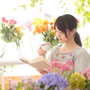 花に囲まれた部屋で読書をする女性の写真素材 [FYI02848454]