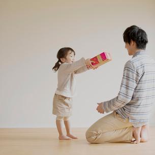 父親にプレゼントを渡す女の子の写真素材 [FYI02848481]