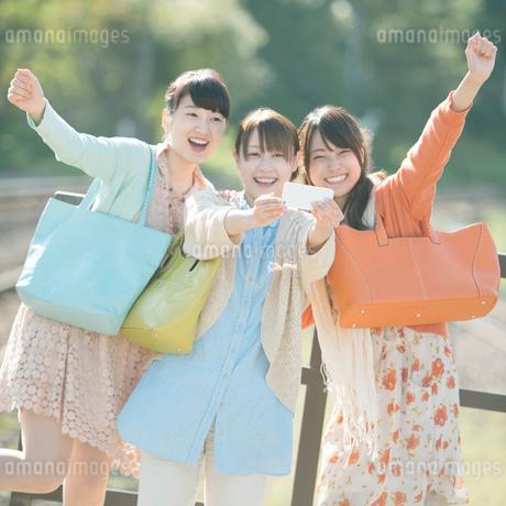スマートフォンで写真を撮る3人の女性の写真素材 [FYI02848556]
