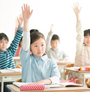 教室で手を挙げる小学生の写真素材 [FYI02848562]