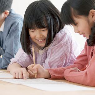 床に寝転び勉強をする小学生の写真素材 [FYI02848574]