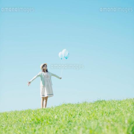 草原で風船を持ち微笑む女性の写真素材 [FYI02848652]