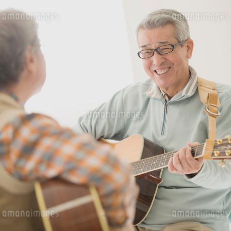 ギターを弾くシニア男性の写真素材 [FYI02848706]