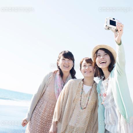 海で写真を撮る3人の女性の写真素材 [FYI02848764]