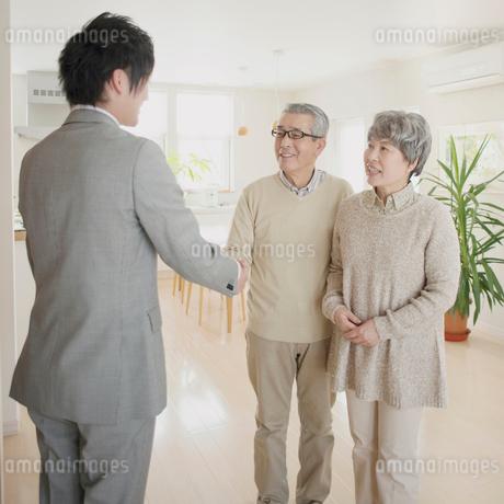 ビジネスマンと握手をするシニア夫婦の写真素材 [FYI02848783]