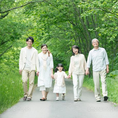 手をつなぎ微笑む3世代家族の写真素材 [FYI02848823]