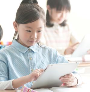 教室でタブレットPCを操作する小学生の写真素材 [FYI02848961]