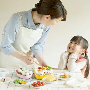 キャラクター弁当を作る母親と微笑む女の子の写真素材 [FYI02849081]