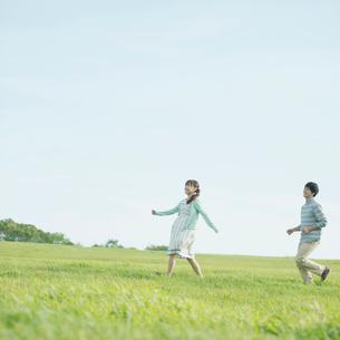 草原を走るカップルの写真素材 [FYI02849146]