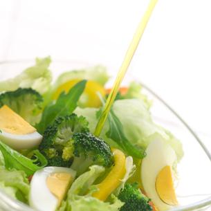 ドレッシングをそそぐ野菜サラダの写真素材 [FYI02849156]