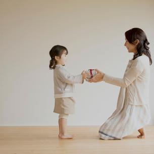 母親にプレゼントを渡す女の子の写真素材 [FYI02849192]