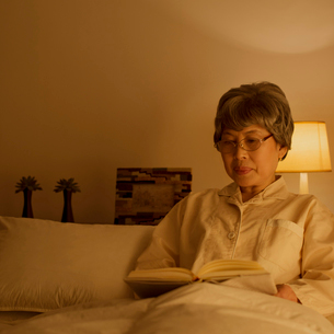 ベッドで本を読むシニア女性の写真素材 [FYI02849266]