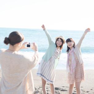 海で写真を撮る3人の女性の写真素材 [FYI02849280]