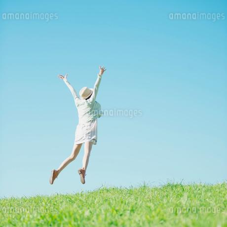 草原でジャンプをする女性の後姿の写真素材 [FYI02849308]