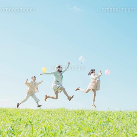 風船を持ち草原でジャンプをする3人の女性の写真素材 [FYI02849360]