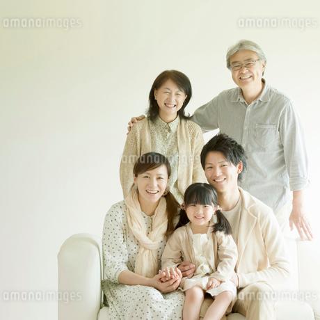 ソファーに座り微笑む3世代家族の写真素材 [FYI02849383]