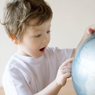 地球儀を見るハーフの男の子の写真素材 [FYI02849387]