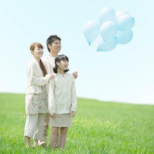 草原で風船を持ち微笑む家族の写真素材 [FYI02849388]