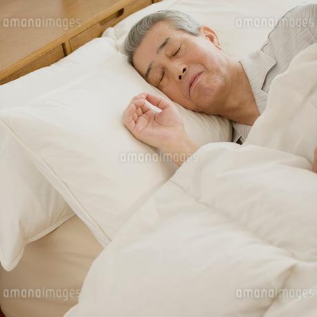 ベッドで眠るシニア男性の写真素材 [FYI02849404]
