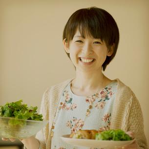 サラダとワンプレートを持ち微笑む女性の写真素材 [FYI02849422]