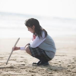 砂浜に絵を描く女子校生の写真素材 [FYI02849862]