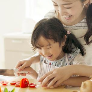 母親に野菜の切り方を教えてもらう女の子の写真素材 [FYI02849876]