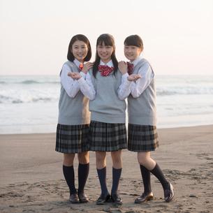 砂浜で微笑む女子校生の写真素材 [FYI02849878]