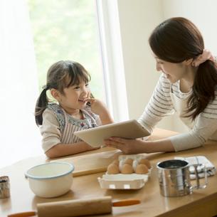 タブレットPCでレシピを調べる親子の写真素材 [FYI02849889]