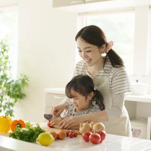 母親に野菜の切り方を教えてもらう女の子の写真素材 [FYI02849898]